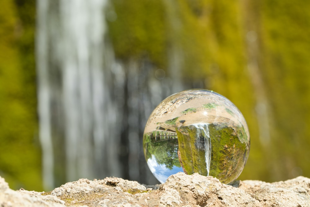 Spère en verre qui reverse l'image d'une cascade d'eau
